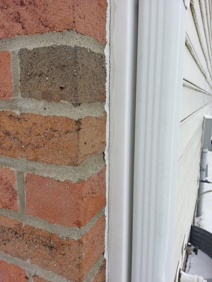 Leak Where Brick Wall Meets Vinyl Siding Building
