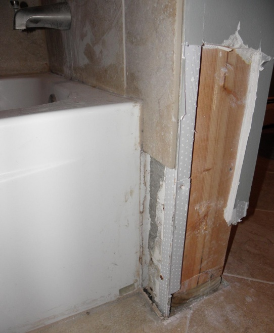 Water issue in bathroom at base of the tub and shower plumbing wall-corner.jpg