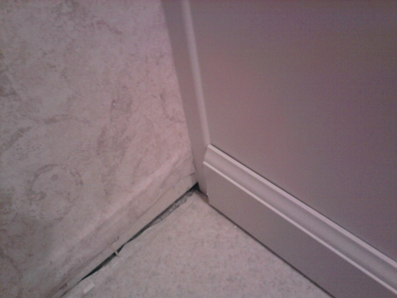 Gap Install Baseboard Over Around Existing Trim Of Bathroom Vanity Flush