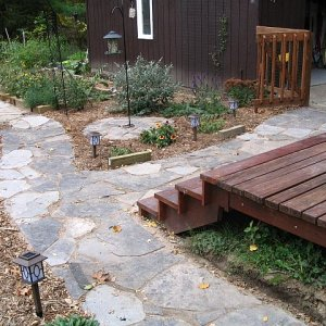 Done for this year.  Then we rototilled, making sure there was the important slope away from the foundation, and put down fabric and cedar mulch...