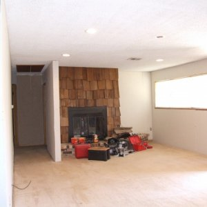 Fireplace after new drywall installed. (note 6 new recessed lights and a ceiling fan brance in the center)