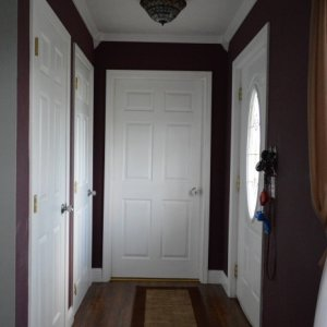 Living Room Entryway (Before). New paint is on the wall showing in the left, all the rest is the old paint (dark reddish purple). Changes to come:...