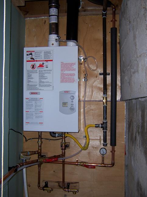 """Completed install.   Note the pressure gauge which will aid in potential troubleshooting scenarios. I am on well water so I have a gauge before and after the heater.   The condensate line may come out as the heater has yet to sweat, even at -25 degrees C. It's currently running to the furnace condensate pump.  The intake pipe is 3"""" ABS which I recovered from the old water heater."""