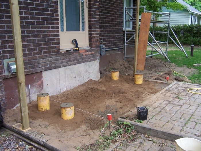 Footings go four feet down, belled out at the bottom, reinforced with rebar.