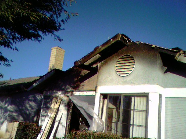 Front of the house after the fire. Firemen did most of the roof damage getting smoke & heat out. No one was home, dogs got out dog door. Our neighbor put out the fire with garden hoses! Important that I had other bedrooms doors closed!