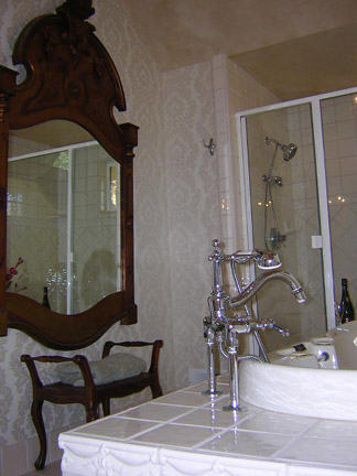 I was out one Sunday antiquing and ran across this stunning mirror. It is very tall with hand carved cherubs and a large plume head piece.  So I decided to design a bathroom to fit the mirror. The tub filler is from Kohler's Antique collection.  The floors are Crema Marfil marble.  The vanity was an antique sideboard that I had plumbed. The wall sconces are also from a flea market and were the perfect touch for this Victorian themed French bath.  See vanity next pic.