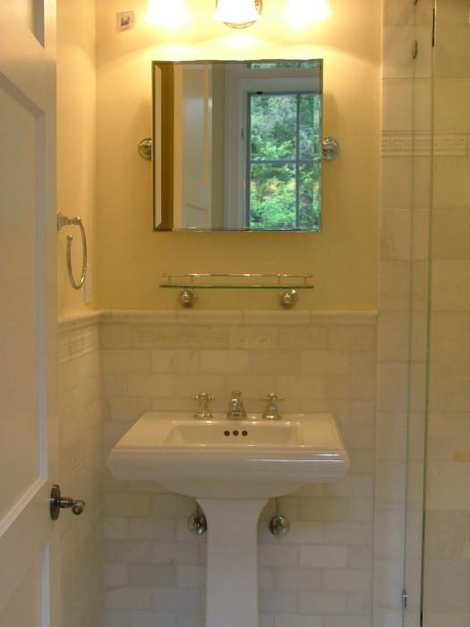 This bath is the guest bath. The walls were tiled in Jeffrey Courts Grammercy Park collection.  The subway shaped tiles are made from quartz.   I used Carrerra marble on the floors and the walls were painted a very soft cantalope color (Benjamin Moore Cornsilk 198)
