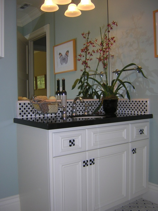 This bath was inspired by one of my favorite TV shows, Happy Days. I love anything black and white checkerboard.  The counter is black granite with American Olean checkboard marble mosaic backsplash. The wall color is Benjamin Moore Quite Moments 1563.