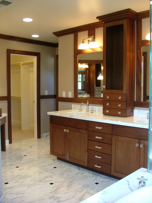 This bathroom was inspire by a luxury 30's ocean liner. Cabinets are custom made from Mahogany wood with Carerra marble counters and floors. Faucets are from Perren & Rowe's Michael Berman collection in polished nickel.