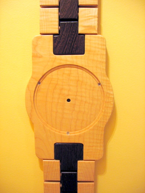 """This is a clock I built that looks like a wristwatch. It is 36"""" tall. The lighter wood is tiger maple, the dark wood is wenge from Africa."""
