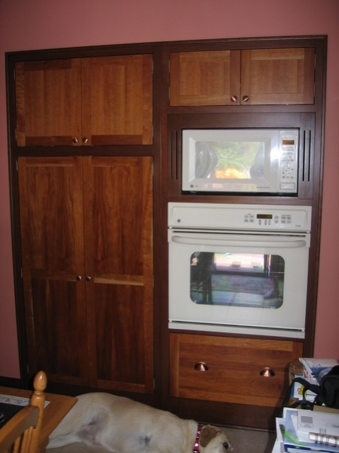 "This is part of my kitchen. This wall is the back wall of the garage. When I redid the kitchen in 2003, I cut a hole in this wall and framed in an opening for this pantry and oven cabinet. The faceframes overlap the drywall by 3/4"". The cabinets are cherry, shaker style. Doors and drawerfronts are natural finish, frames are darker stain. All the door and drawers are inset with an 1/8"" margin."